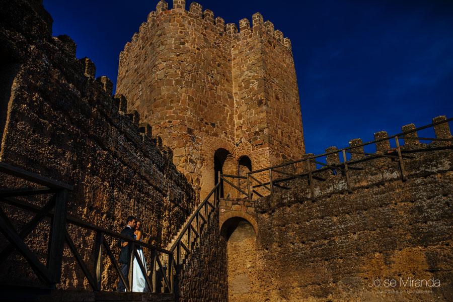 Novios sobre la pasarela de la torre de homenaje del castillo en una fotografía de post-boda en LInares