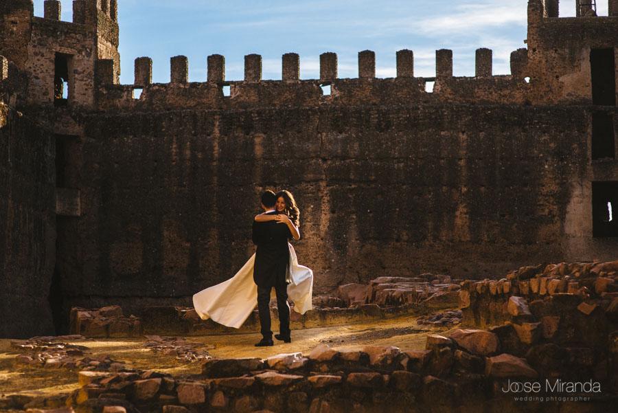 Novio levantando a la novia delante de las almenas de castillo en una fotografía de post-boda en LInares.