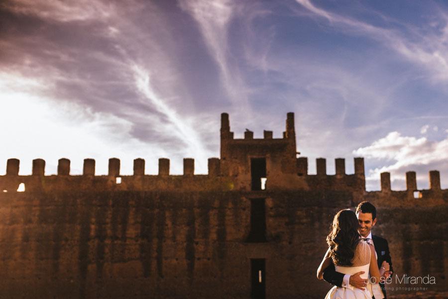 Novios abrazandose entre las paredes del castillo y el cielo