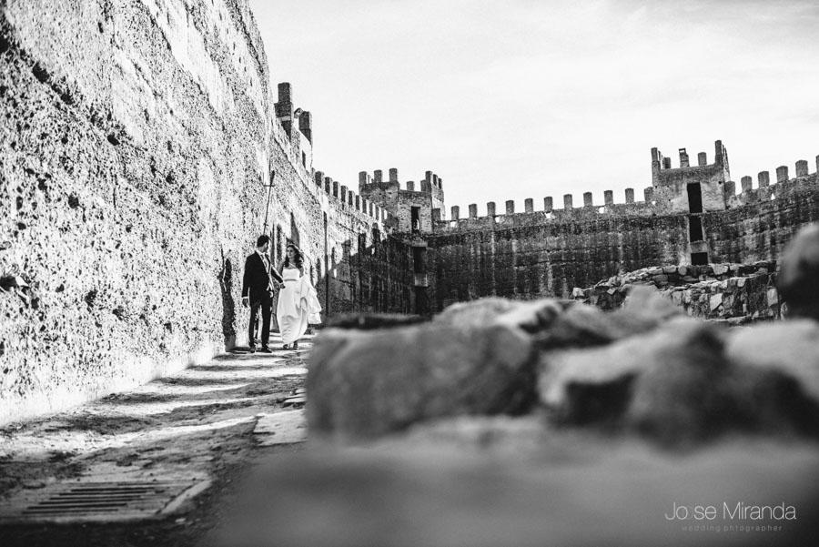 Novios paseando entre las piedras y las almenas del castillo en una fotografía de post-boda en Linares