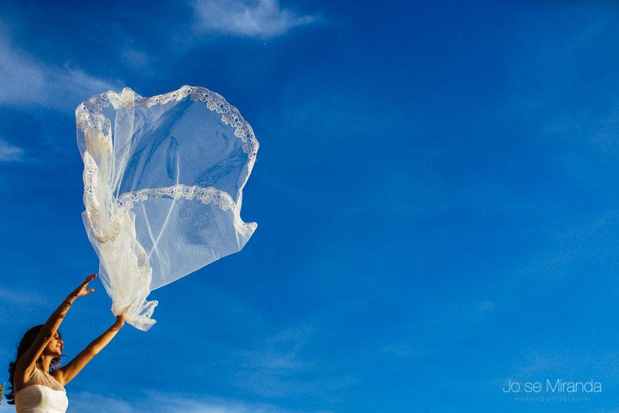 Novia jugando con su velo frente el cielo azul en una fotografía de post-boda en Linares