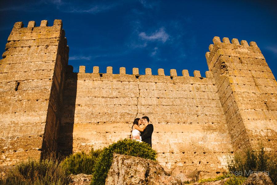 Novios besándose frente los muros del castillo en una fotografía de post-boda en Linares