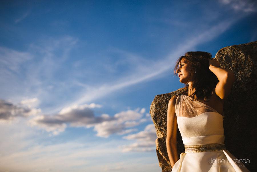 Novia echada sobre las piedras del castillo y el cielo azul en una fotografía de post-boda en Linares