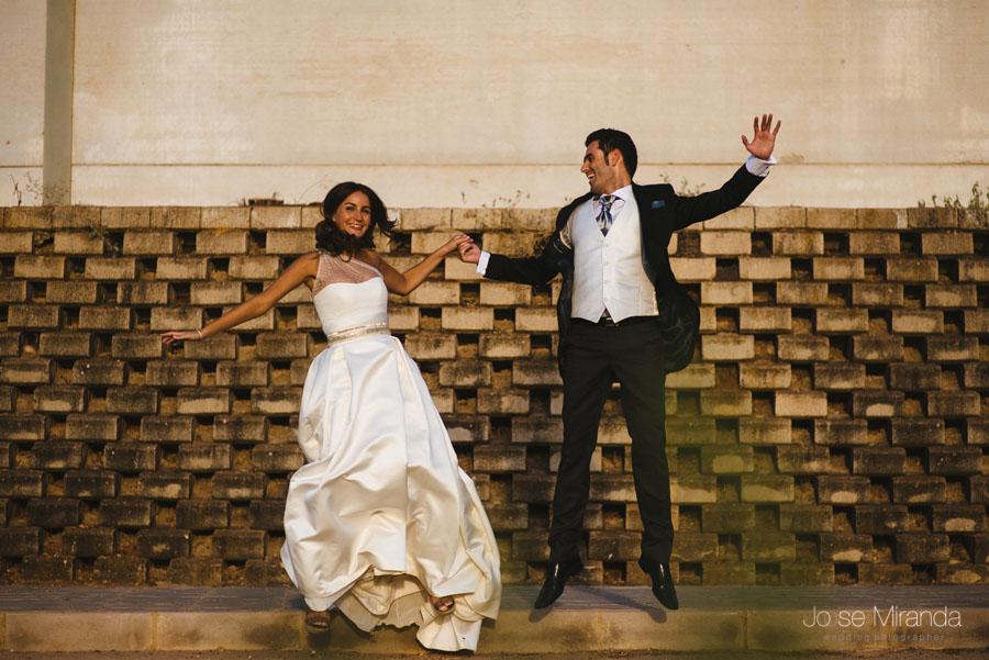 Novios saltando mientras se rien delante de un muro de hormigón durante una fotografía de post-boda en LInares
