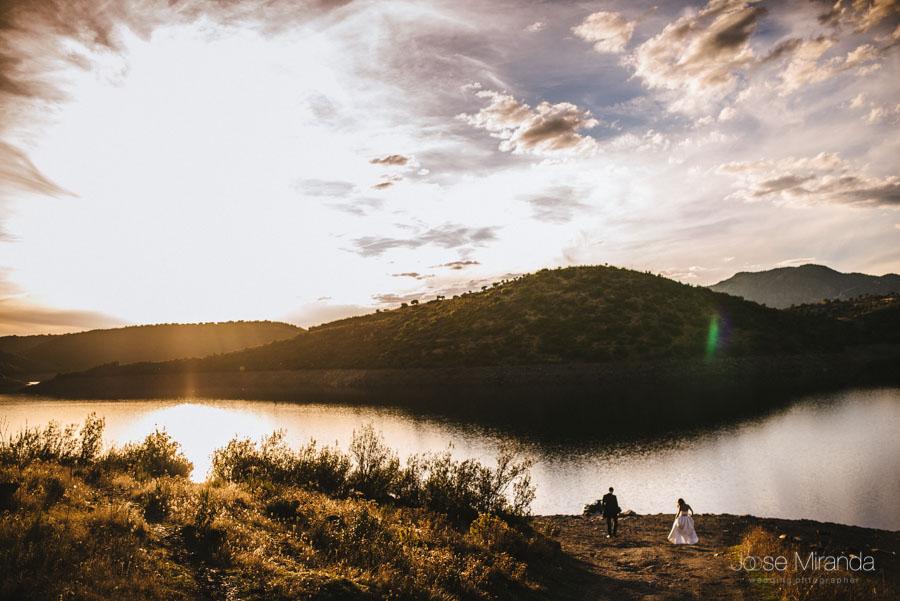 Novios llegando a la orilla de un pantano con el sol poniéndose en una fotografía de post-boda en Linares