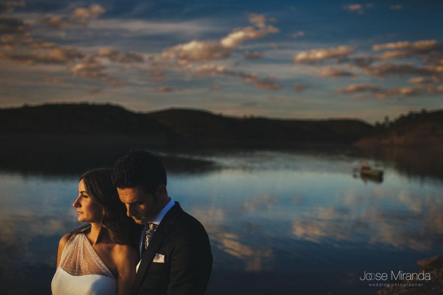 Novios abrazados con el sol en la cara y el pantano al fondo con una piragua en una fotografía de post-boda en Linares