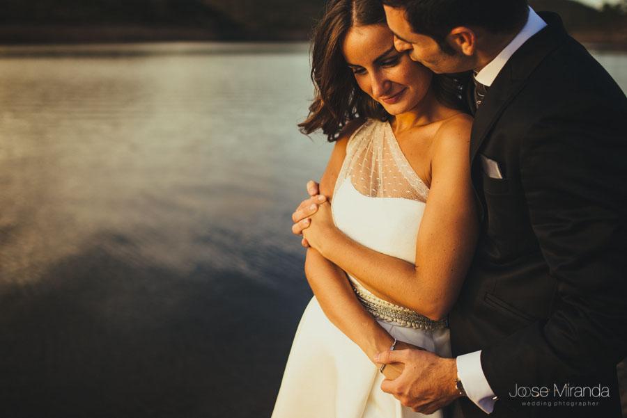 Novios abrazandose en la orilla del pantano en una fotografía de post-boda en Linares