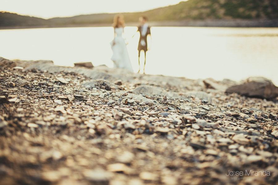 piedras del pantano enfocadas con los novios desenfocados en una fotografía de post-boda en Linares