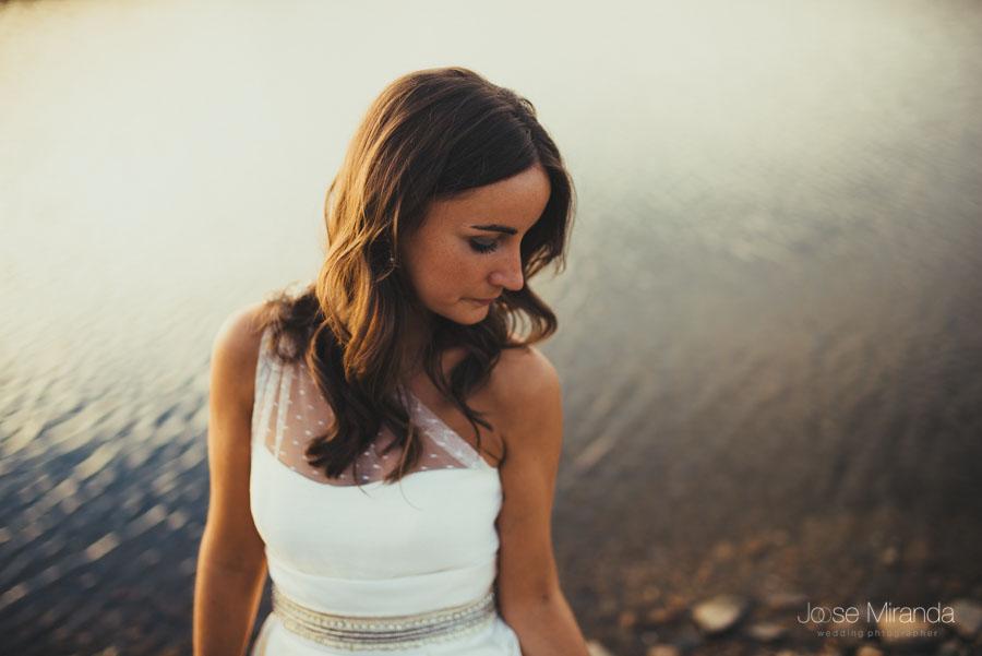 Novia mirándose el vestido a la orilla del pantano en una fotografía de post-boda en LInares