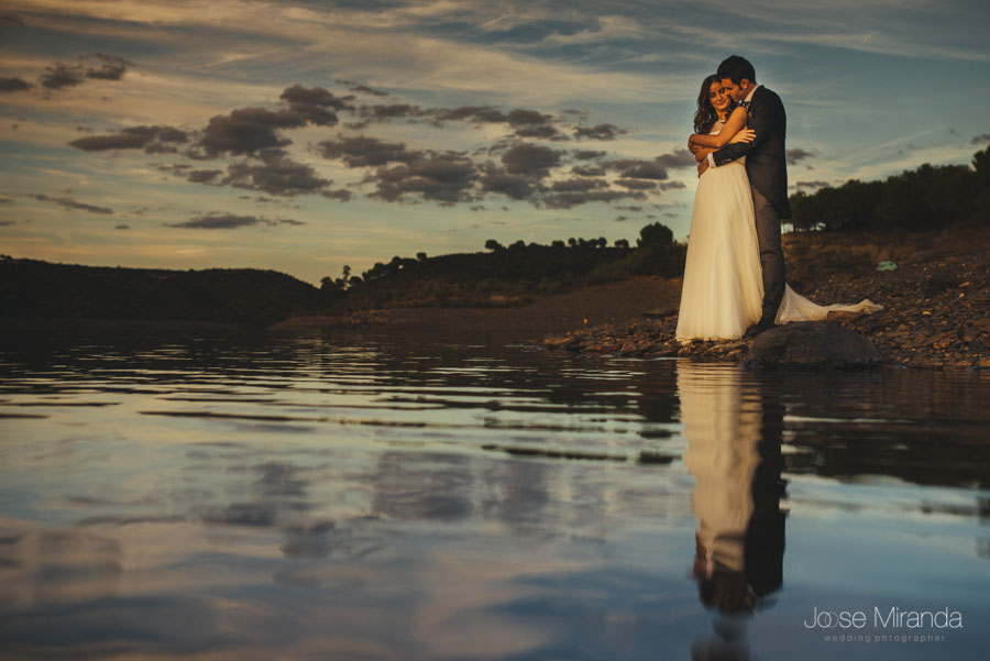 Novios abrazados al borde del agua en una fotografía de post-boda en Linares