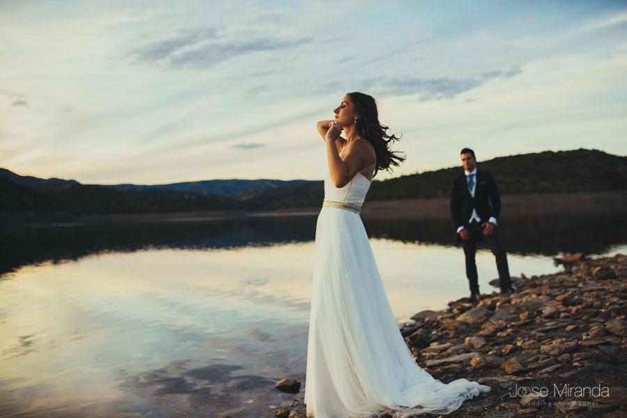 Novia colocándose el pelo mientras su novio la mira en la orilla del pantano en una fotografía de post-boda en LInares