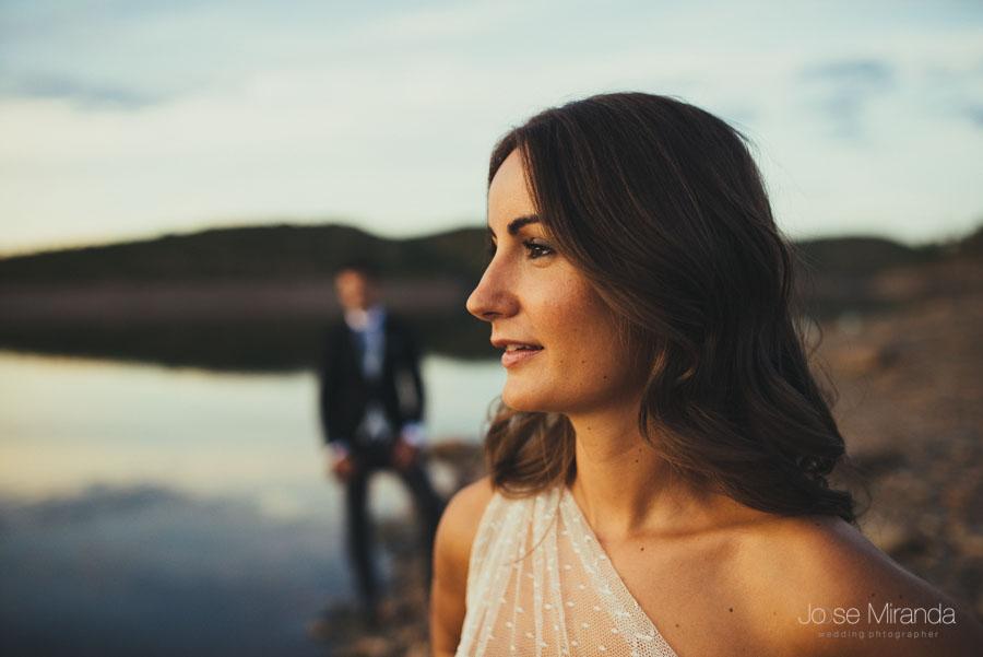 Retrato de novia con el novio al fondo en la orilla del pantano en una fotografía de boda en Linares