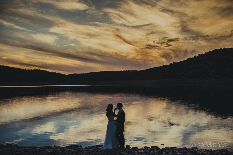 Novios en silueta con el cielo reflejandose en las aguas en una fotografía de post-boda en LInares