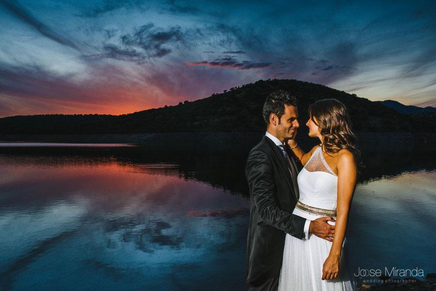 Novios recortados con el cielo rojo del sol poniendose reflejado en el lago en una fotografia de post-boda en Linares