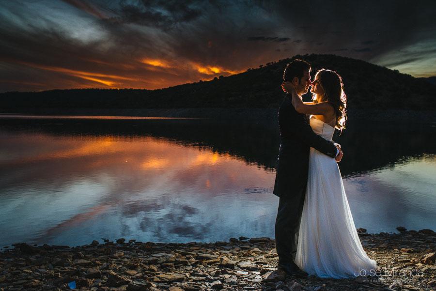 Novios abrazándose con el cielo encendido rojo en una fotografía de post-boda en Linares
