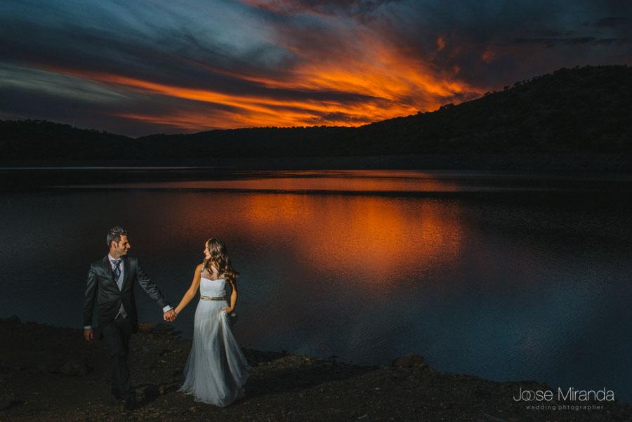 Novios caminando por la orilla y el cielo rojo reflejandose en las aguas en una fotografía de post-boda en LInares