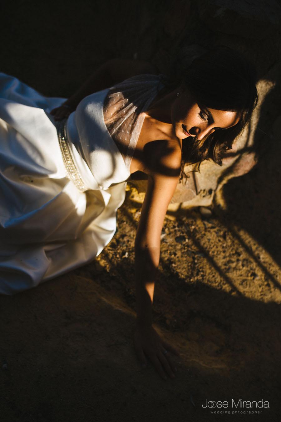 Novia entre los rayos de sol que se cuelan por las ventanas del castillo en una fotografía de post-boda en Linares
