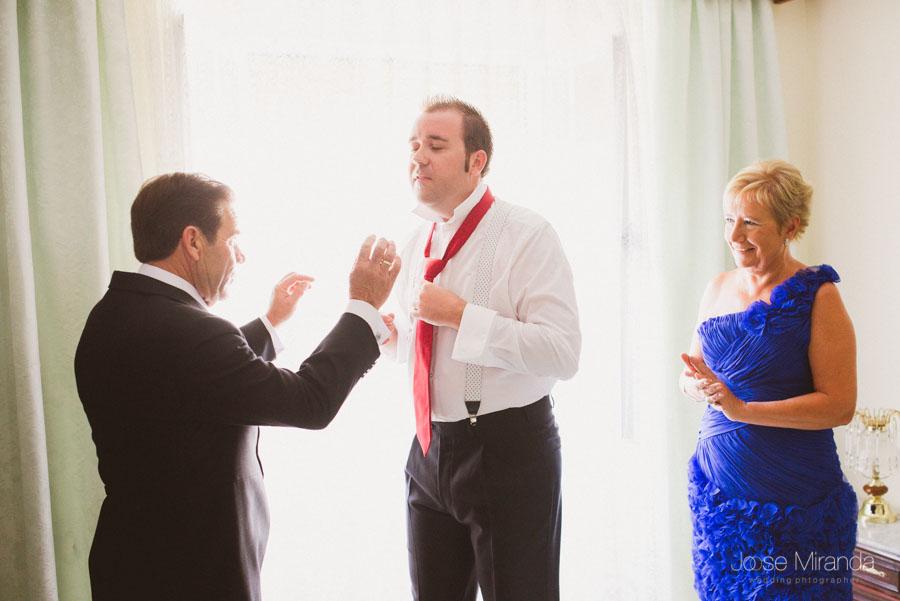 El padre del novio haciendo el nudo de la corbata en una fotografía de boda en Valenzuela