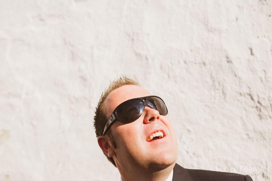El novio con gafas y una pared blanca de fondo
