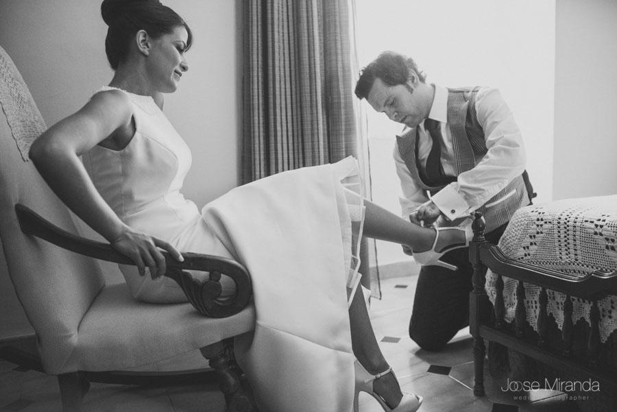 El hermano de la novia abrochando los zapatos de la novia