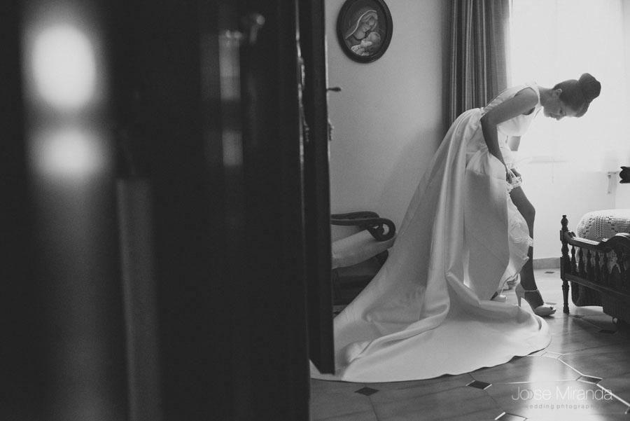 La novia colocándose la liga mientras se arregla