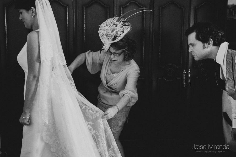 La madre y el hermano colocando el velo de la novia