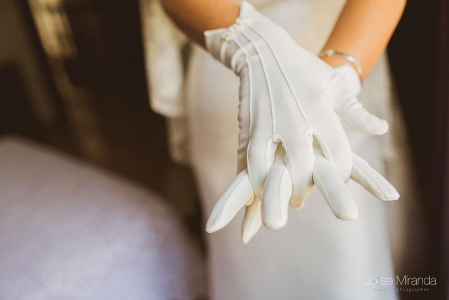 La novia colocándose los guantes mientras se termina de arreglar