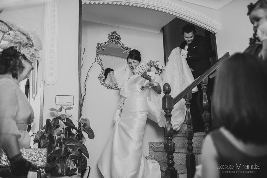 La novia bajando por las escalesras mientas la esperan sus amigas
