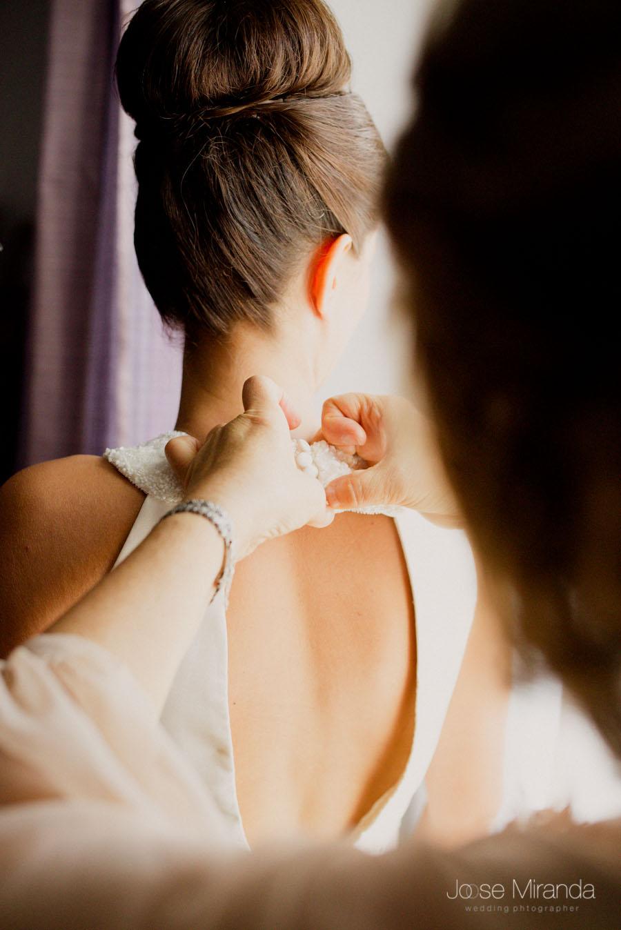 La madre abrochando el vestido de la novia
