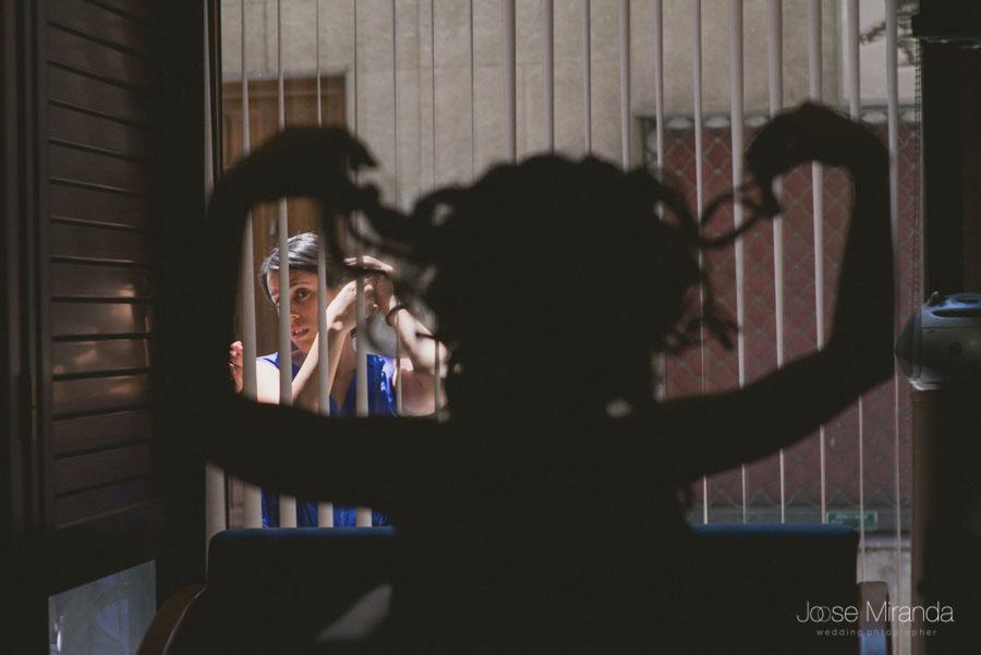 Amiga de la novia por la ventana mientras la novia le hace burlas con el pelo en una fotografía de boda en Martos de Jose Miranda