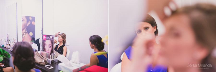 Amiga de la novia mirando como la maquillan en una fotografía de boda en Martos