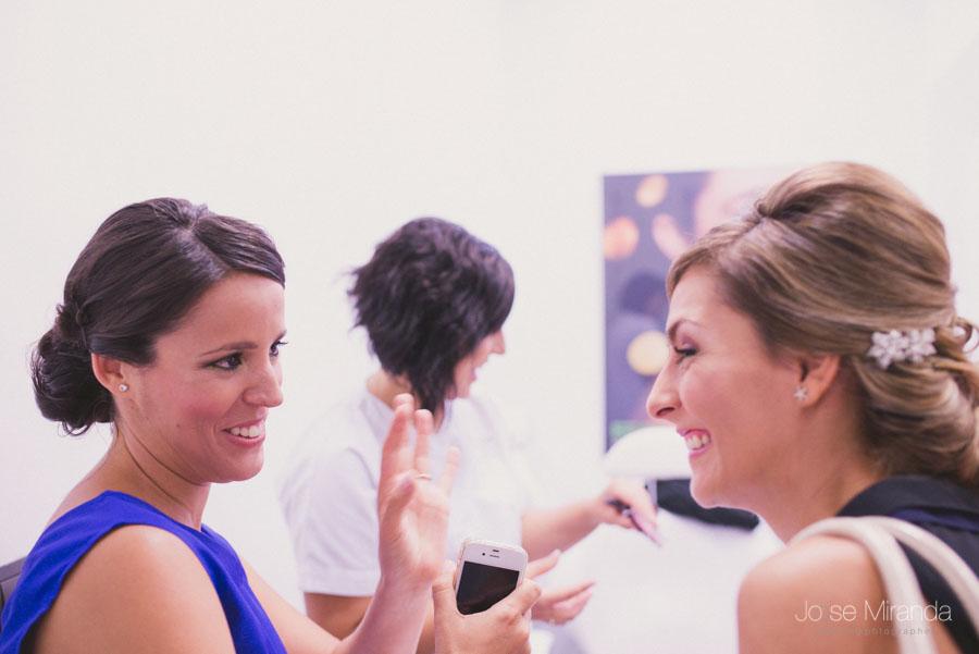 Novia y su amiga terminando de maquillarse y riendo