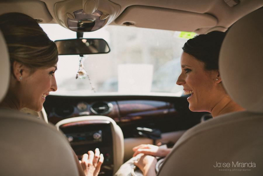 Novia y su amiga en el coche para ir a vestirse para la celebración