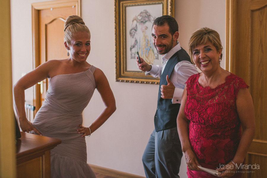 La familia del novio riendose mientras el novio comienza a vestirse en una fotografía de boda en Martos de Jose Miranda
