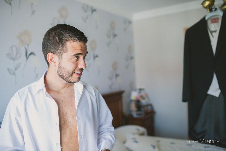 El novio comenzando a vestirse en una fotografía de boda en Martos