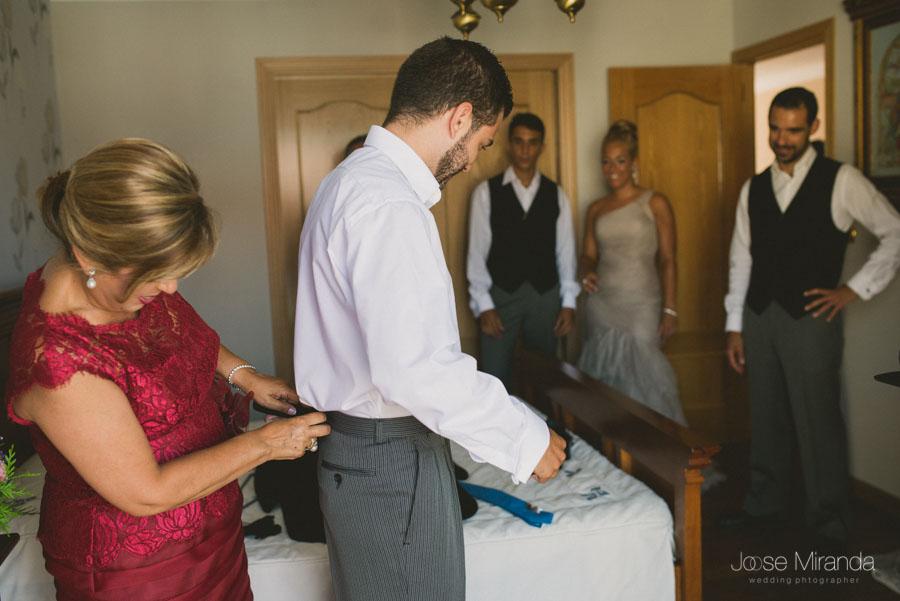 La madre del novio ayudandole a vestirse mientras su familia lo mira en una fotografía de boda de Jose Miranda