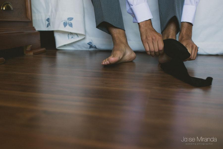 El novio poniéndose los calcetines en una fotografía de boda de Jose Miranda