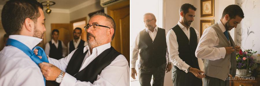 El padre y el hermano del novio ayudandole a vestirse con la corbata y el chaleco de novio