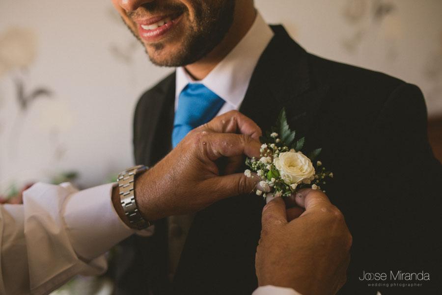 Las manos del padre poniendole las flor en la solapa y la sonrisa del novio en una fotografía de boda en Martos