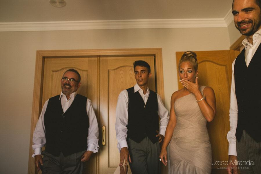 Los hermanos y el padre mirando al novio mientras se viste todos expectantes