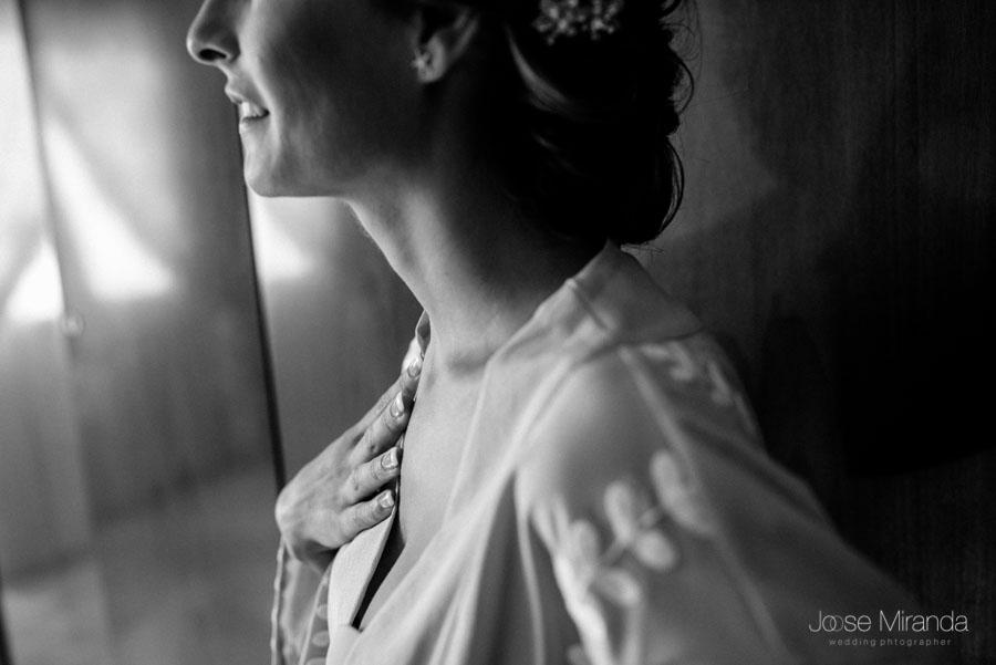 La novia emocionada con su mano en el pecho mientras mira su vestido de novia