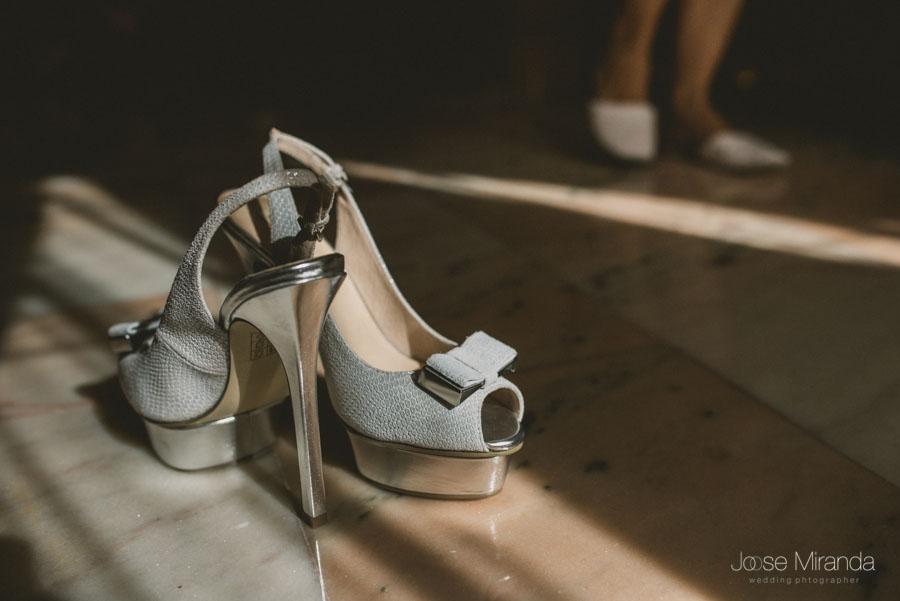 Los zapatos y los pies de la novia mientras se prepara para vestirse