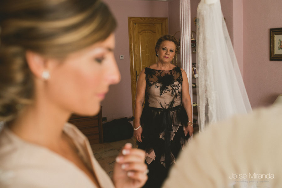 Madre de la novia mirandola emocionada, con el velo al fondo y ella vistiendose