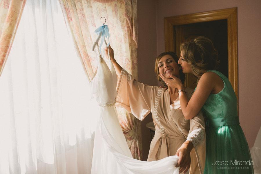Novia cogiendo el vestido para vestirse mientras su hermana la besa llena de felicidad