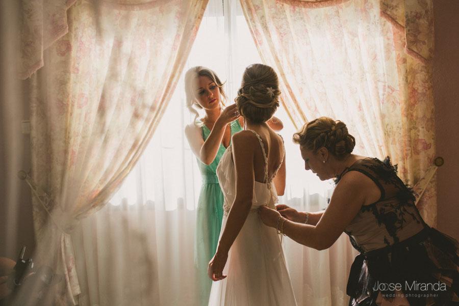 La hermana y su madre ayudando a la novia a vestirse a contraluz en una fotografía de boda en Martos
