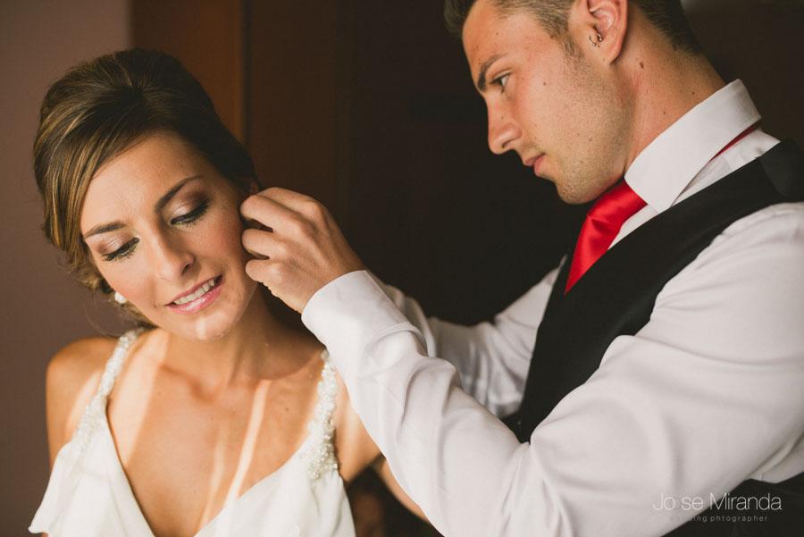 Hermano de la novia poniendo los pendientes de novia en una fotografía de boda en Martos