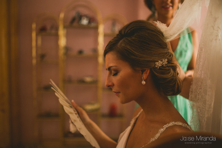 Mariah con un gesto serio y abanicandose mientras le colocan el velo de novia y su hermana la mira