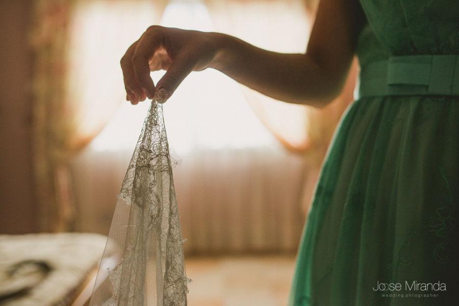 La hermana cogiendole el velo a la novia en una fotografía de boda en Martos