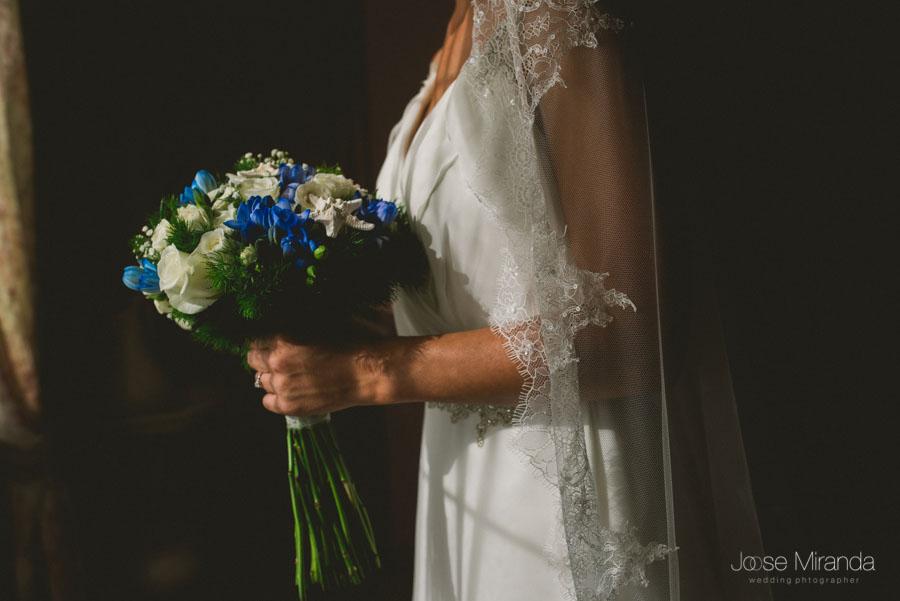 La novia sostiendo su ramo iluminado por el sol