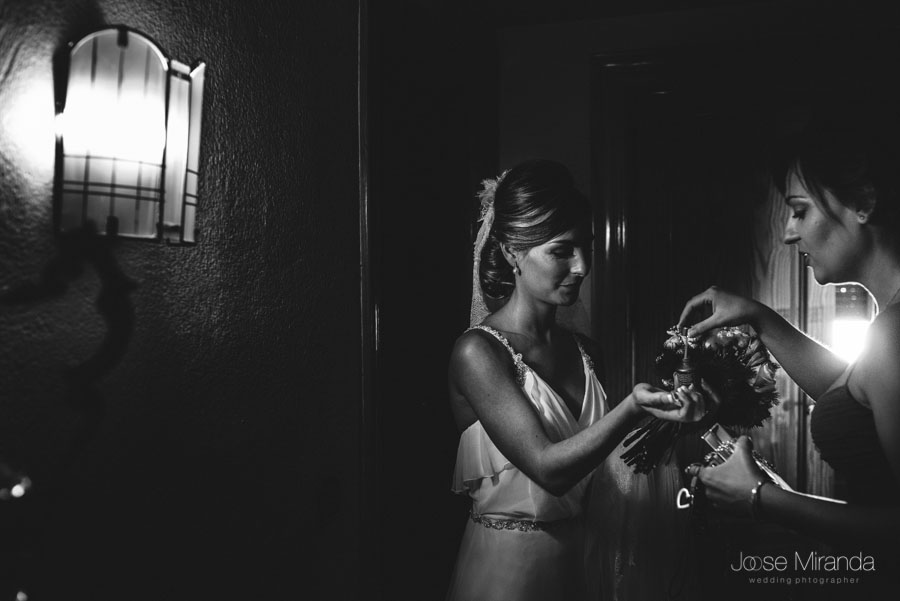 Mariah y su prima Marta dando los últimos toques al ramo de novia en una fotografía de Jose Miranda